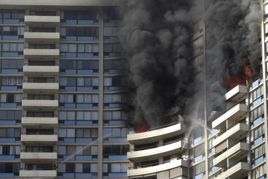 Firefighters on several balconies spray water upwards while trying to contain a fire at the Marco Polo apartment complex, Friday, July 14, 2017, in Ho...