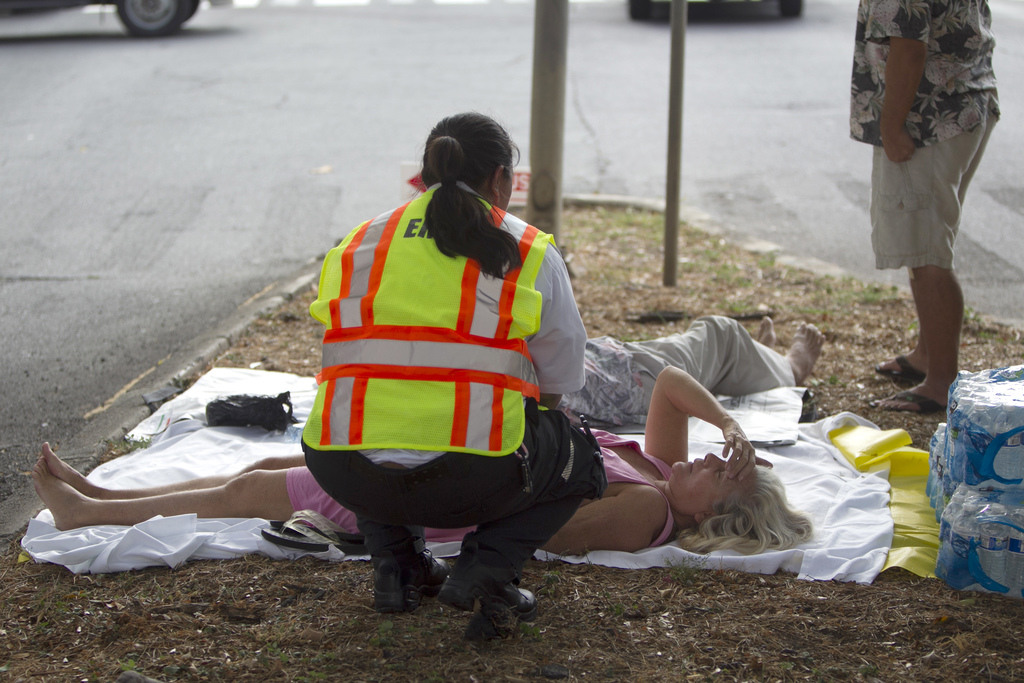 A paramedic checks on a woman, lying on a median, after she and others exited the Marco Polo apartment complex as firefighters continue to battle a bl...