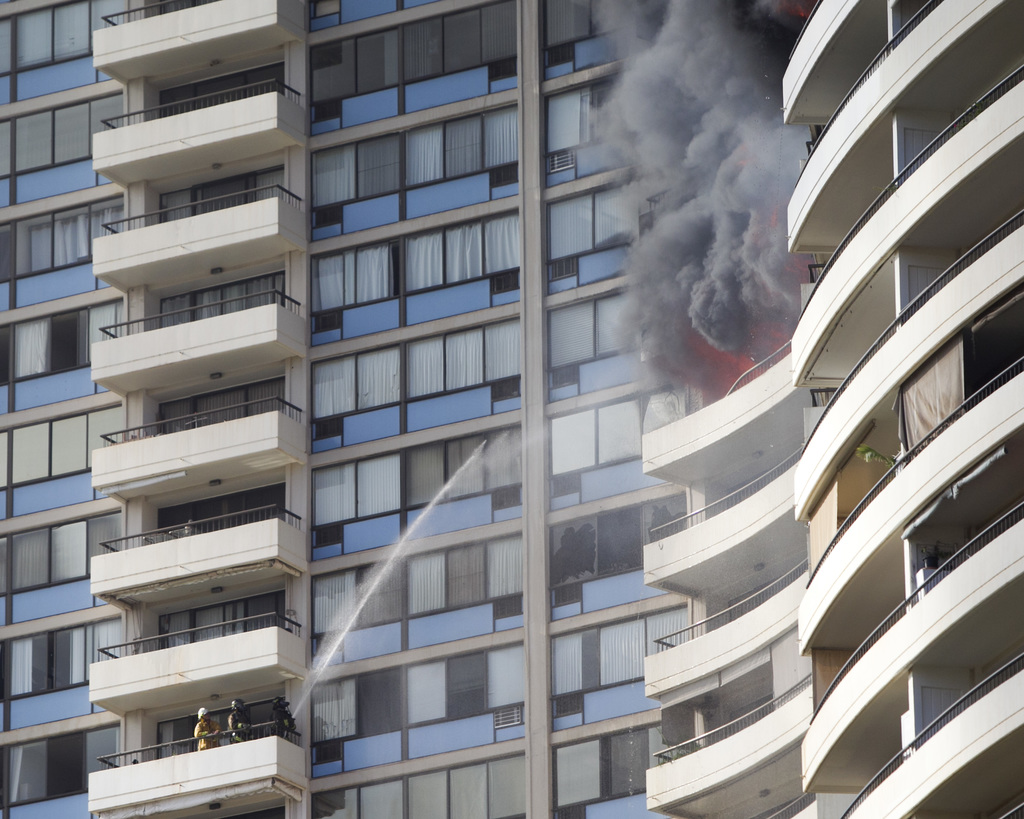 Firefighters on a lower balcony spray water upwards while trying to contain a fire at the Marco Polo apartments, Friday, July 14, 2017, in Honolulu. (...