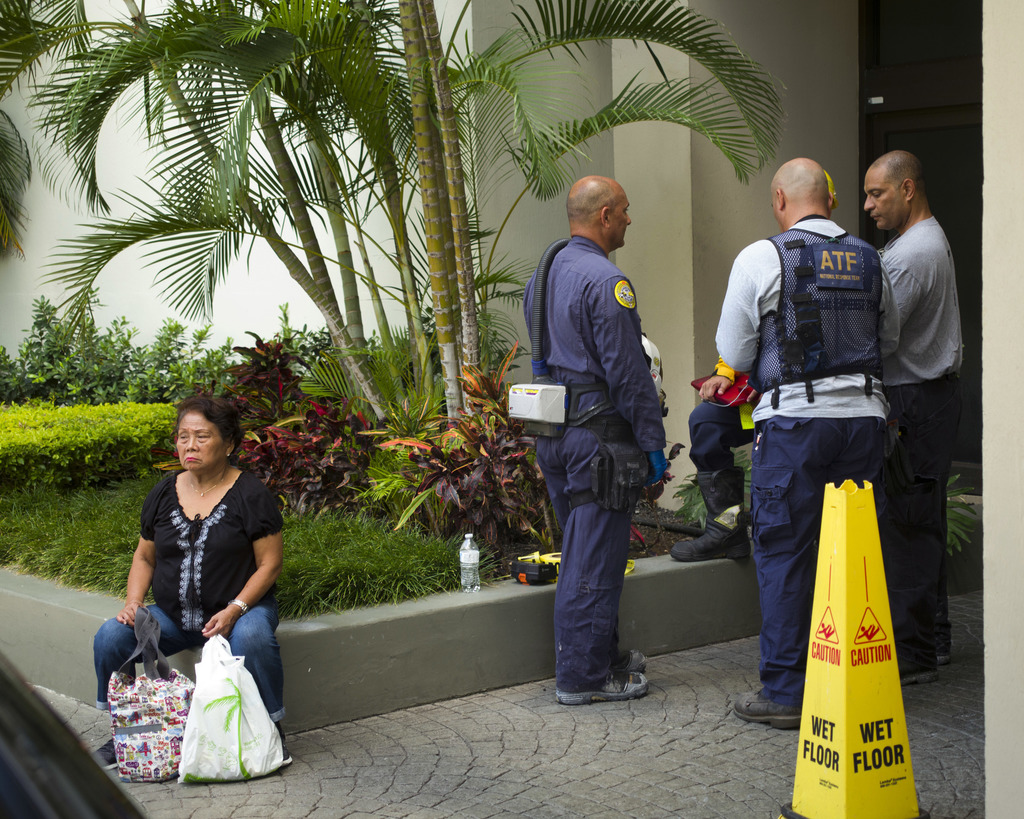 A Bureau of Alcohol, Tobacco, Firearms and Explosives agent, right, and several fire officials stand outside the Marco Polo residence, Saturday, July ...