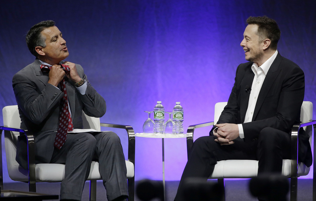 Nevada Republican Gov. Brian Sandoval takes off his tie as he tells Tesla and SpaceX CEO Elon Musk he planned to take it off when Musk was introduced ...