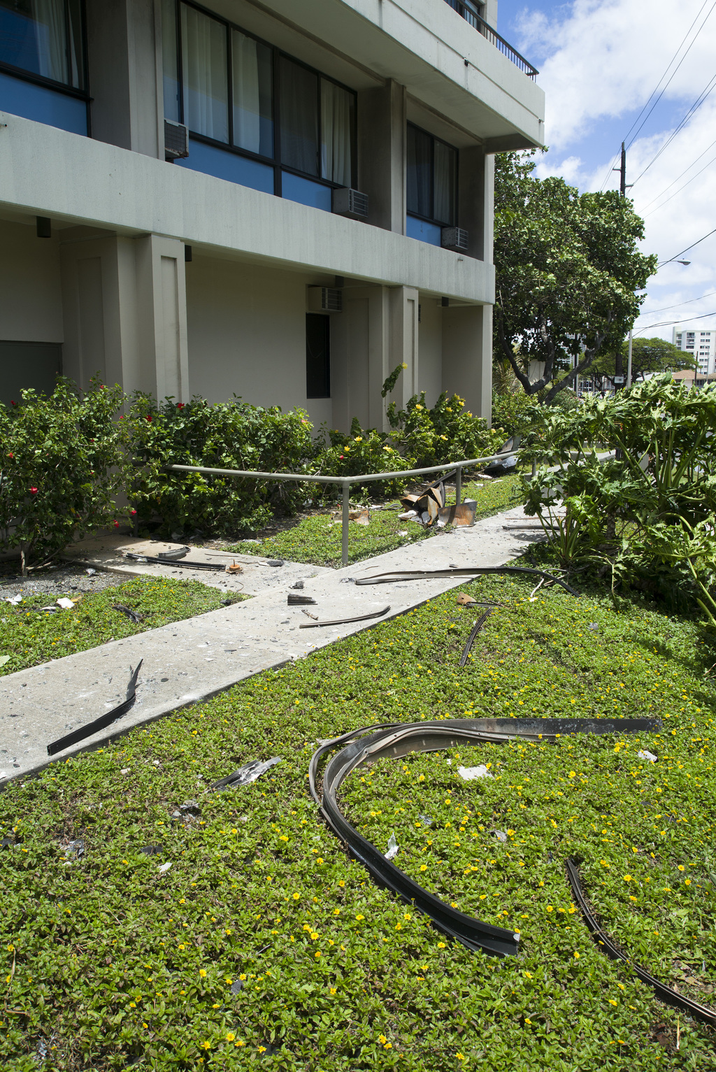 Debris that fell from a fire at the Marco Polo residence lays on the front lawn of the building, Saturday, July 15, 2017, in Honolulu. A fire broke ou...