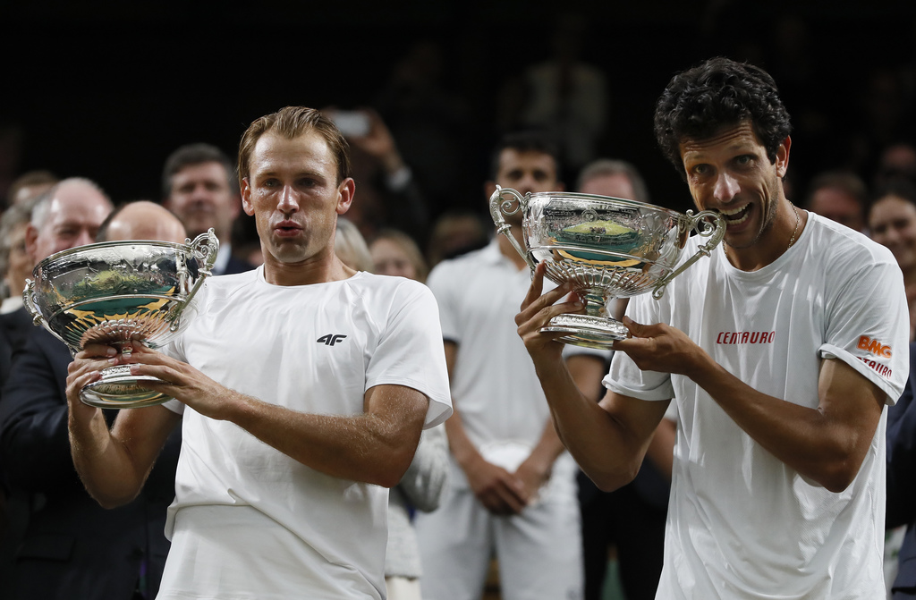 Poland's Lukasz Kubot, left, and Brazil's Marcelo Melo hold up their winners trophies and pose for the media after defeating Austria's Oliver Marach,