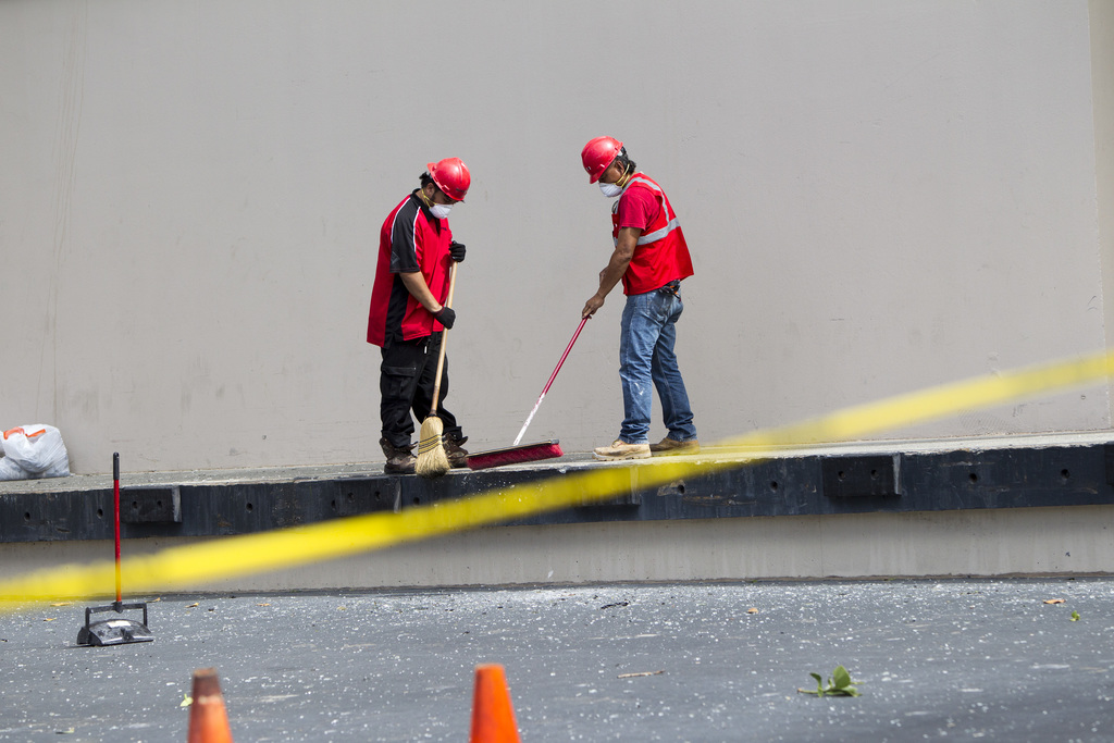 Contractors sweep up the fallen debris after a deadly fire swept through the Marco Polo residence, Saturday, July 15, 2017, in Honolulu. The fire star...
