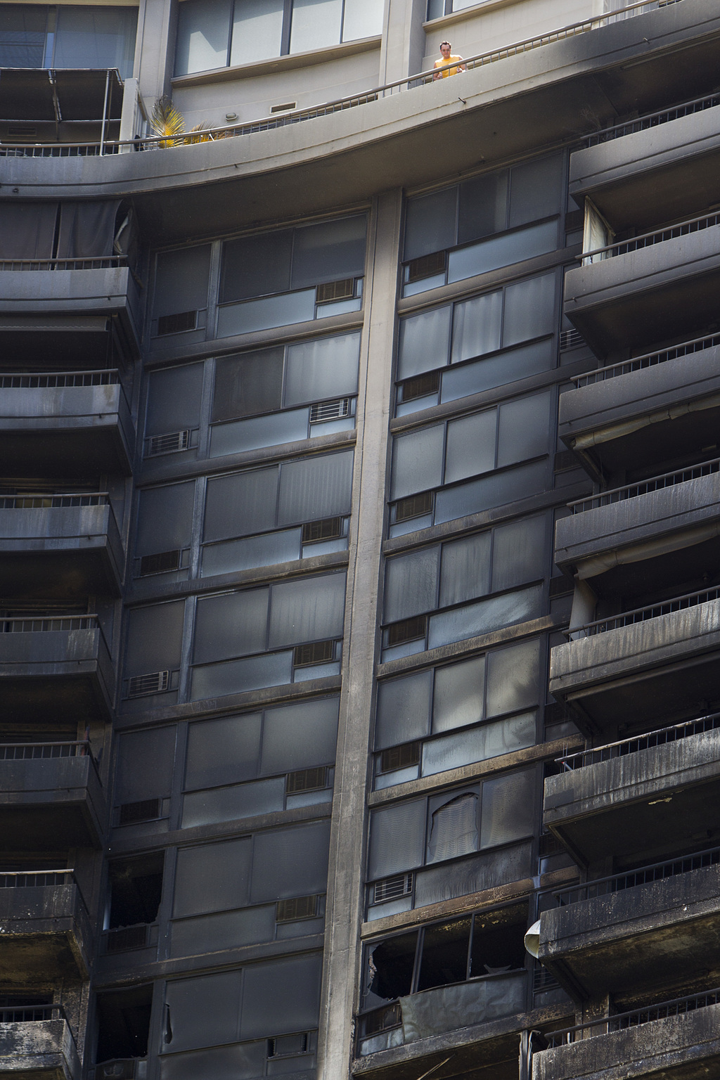 A man looks off his balcony at the the damage left from a deadly fire that destroyed several floors of the Marco Polo residence, Saturday, July 15, 20...