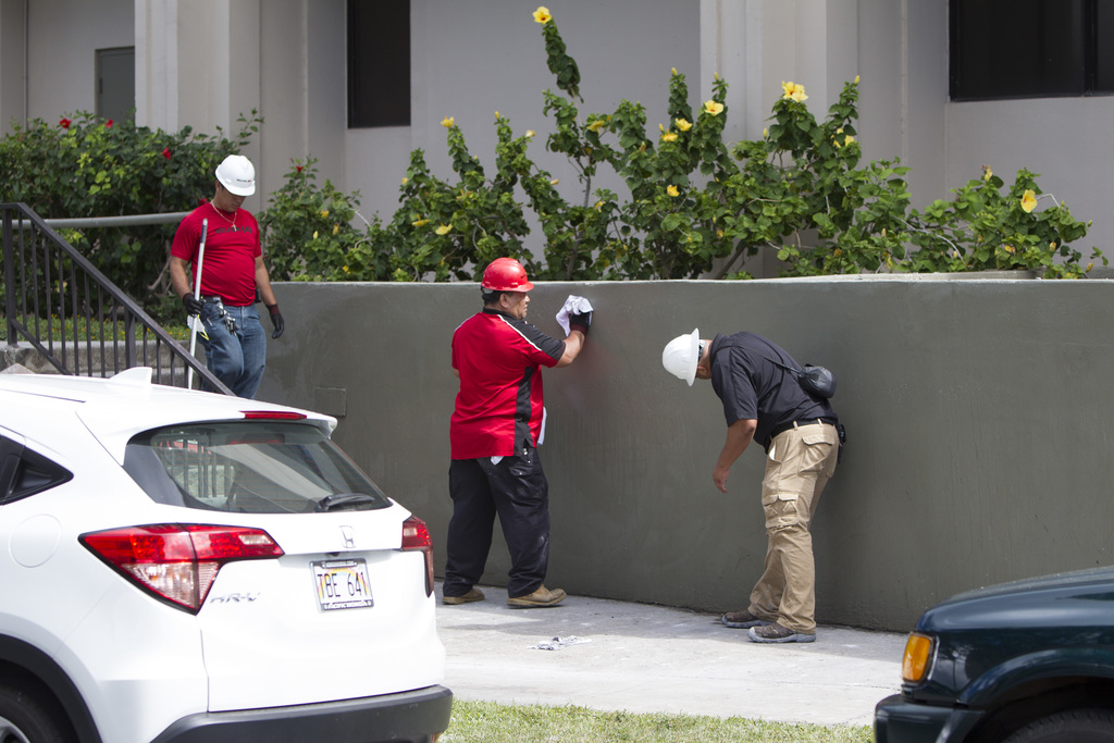 Contractors clean the walls outside the Marco Polo residence, Saturday, July 15, 2017, in Honolulu. A deadly fire started on the 26th floor of the bui...