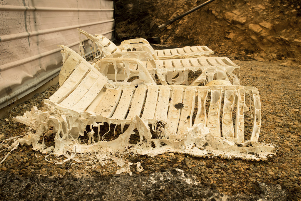 Melted lawn chairs rest outside a residence leveled by the Detwiler fire near Mariposa, Calif., on Wednesday, July 19, 2017. A surging wildfire raced ...