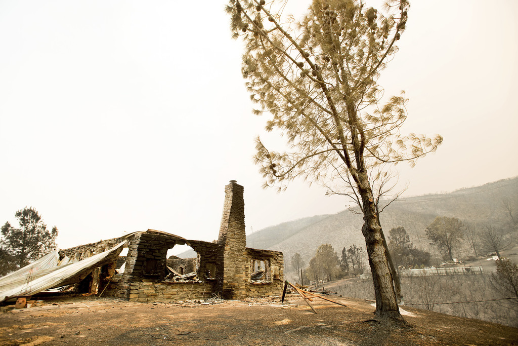 A burned structure stands atop a hill on Yaqui Gulch Road as a wildfire burns near Mariposa, Calif., on Wednesday, July 19, 2017. According to fire of...
