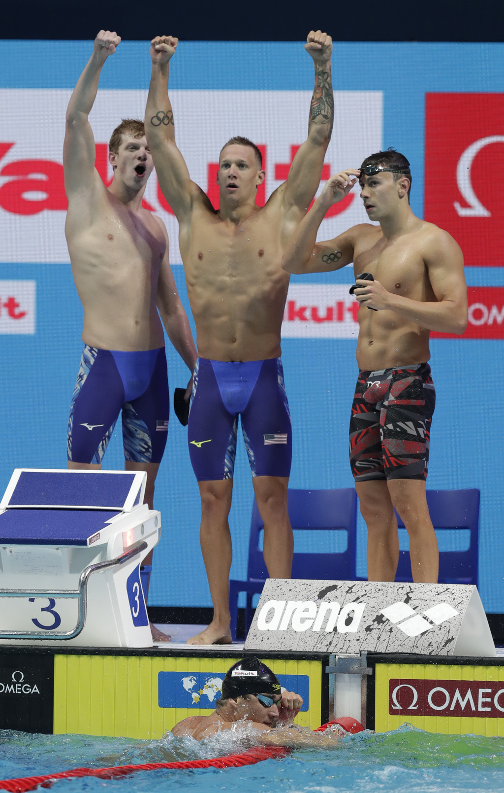 United States' Nathan Adrian, bottom, Townley Haas, top left, Caleb Dressel, top center, and Blake Pieroni, top right, celebrate after winning the gol...
