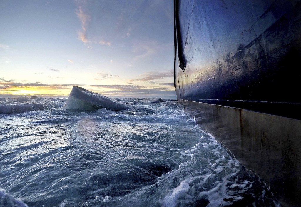 Broken sea ice emerges from under the hull of the Finnish icebreaker MSV Nordica as it sails through the Victoria Strait while traversing the Arctic's...