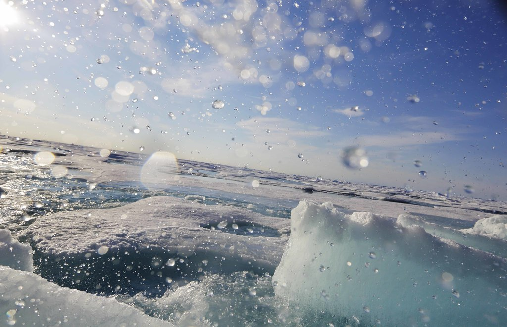 Water sprays as a block of sea ice is broken from the hull of the Finnish icebreaker MSV Nordica as it sails the Victoria Strait while traversing the ...