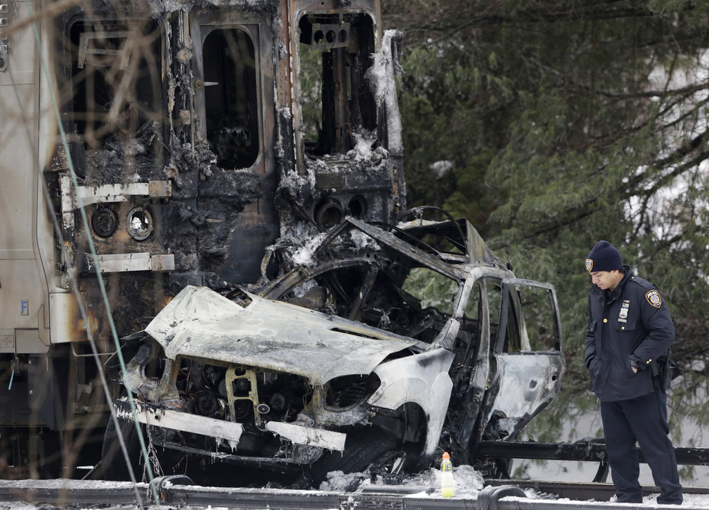 FILE- In this Feb. 4, 2015, file photo, a police officer looks at an SUV that was crushed at the front of a Metro-North Railroad train in Valhalla, N....