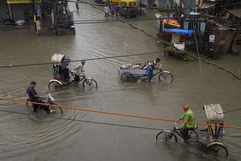 IN this Tuesday, July 25, 2017, file photo, Indian rickshaw pullers wade through a water logged street following heavy rains in Allahabad, India. The ...