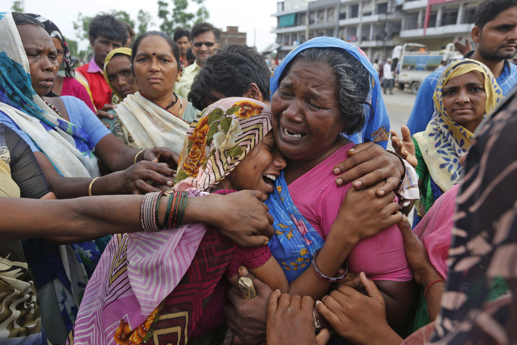 In this Wednesday, July 26, 2017, file photo, Indian flood victim are overcome with emotion after they met at a camp for the displaced in Thara in Ban...