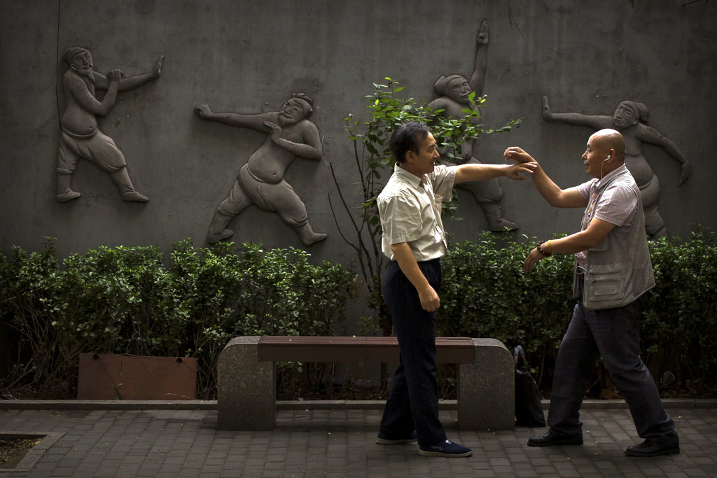 In this Wednesday, July 26, 2017, file photo, two men practice martial arts techniques at a public park in Beijing. Beijing is dotted with urban parks...