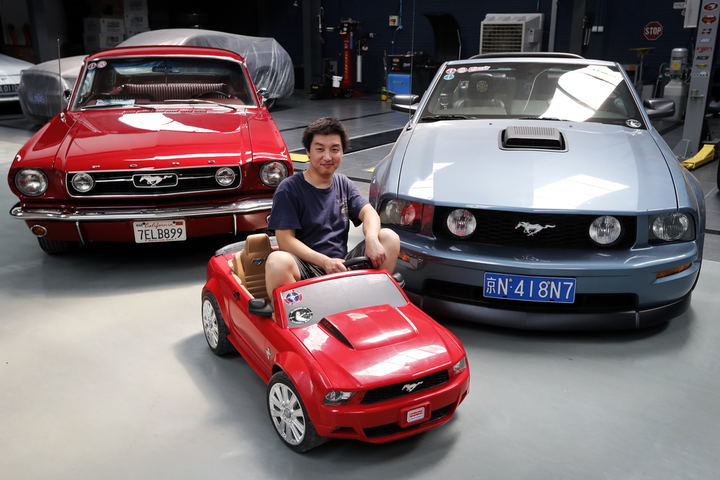 In this Wednesday, June 28, 2017, photo, Guo Xin sits on a toy Mustang as he poses with his 1966 MT GT Fastback, left, and 2005 GT convertible at his ...