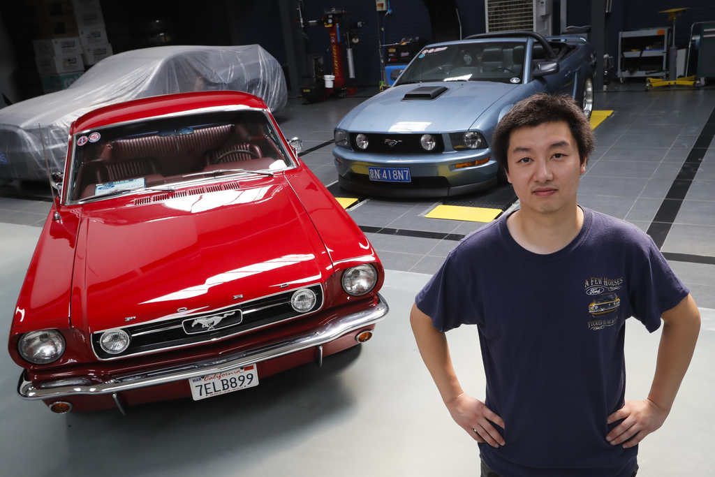 In this Wednesday, June 28, 2017, photo, Guo Xin poses with his 1966 MT GT Fastback, left, and 2005 GT convertible at his garage in Beijing. A former ...