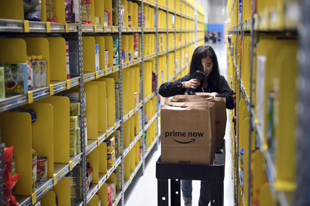 In this Thursday, July 27, 2017, file a staff member collects merchandise for customers' orders from shelves at the newly-opened Amazon Prime Now faci...