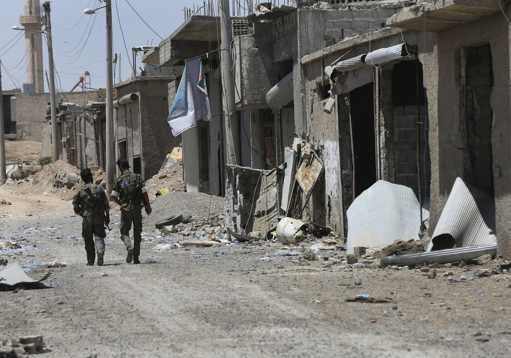 U.S.-backed Syrian Democratic Forces fighters walk past destroyed shops on the front line of the industrial district on the eastern side of Raqqa, Syr...