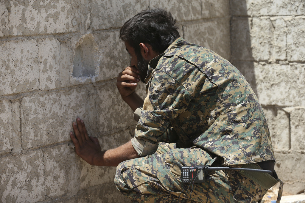 A U.S.-backed Syrian Democratic Forces fighter, looks through a hole on the front line of the industrial district on the eastern side of Raqqa city, n...