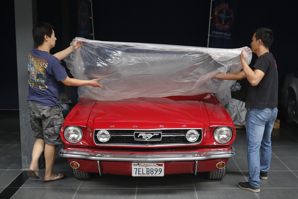 In this Wednesday, June 28, 2017, photo, Guo Xin, left, and Liu Baoguo remove the plastic cover from his 1966 MT GT Fastback at his garage in Beijing....