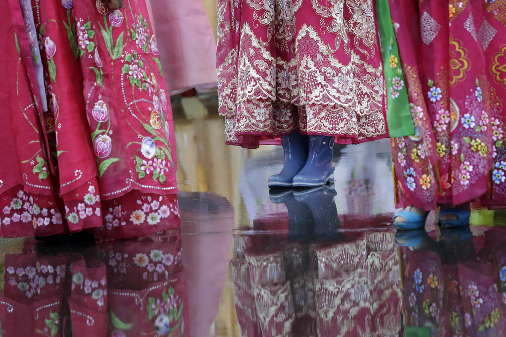 In this Thursday, July 27, 2017, file photo, a university student wears a pair of rain boots with her traditional Korean dress as she waits in the rai...