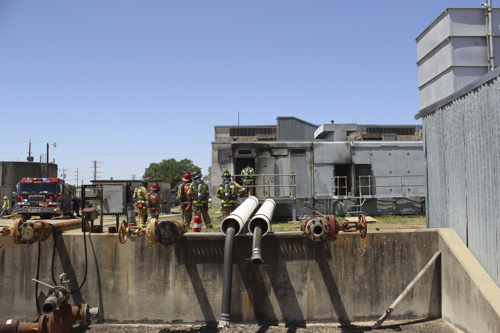 In this photo provide by the Bryan, Texas Fire Department, taken April 29, 2014, Bryan Texas firefighters stand outside the Bryan Texas Utilities Powe...