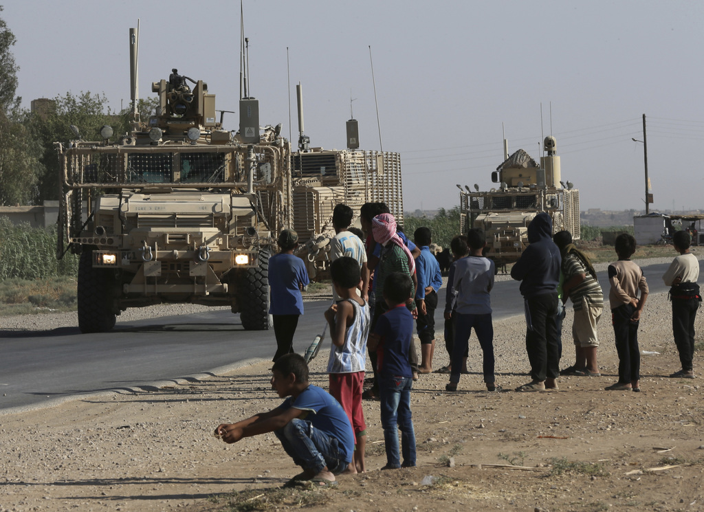 Syrian children and youths gather on a street as they look at a U.S. armored vehicle convoy pass on a road that links to Raqqa city, northeast Syria, ...