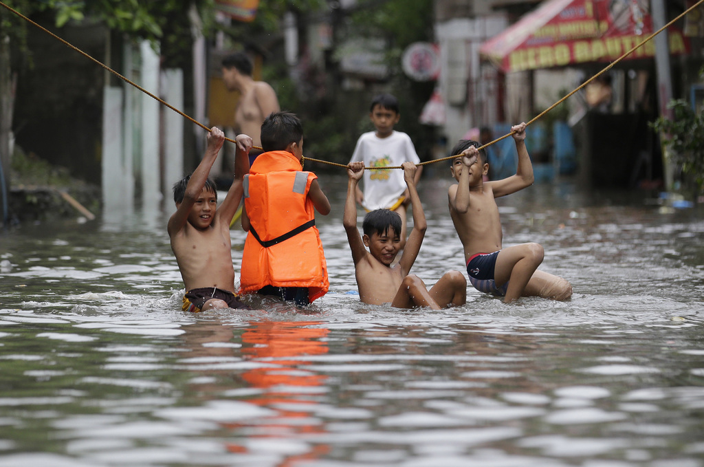 """In this Thursday, July 27, 2017, file photo, boys play outside their flooded homes after heavy rains from tropical storm """"Nesat"""" flooded parts of metr..."""