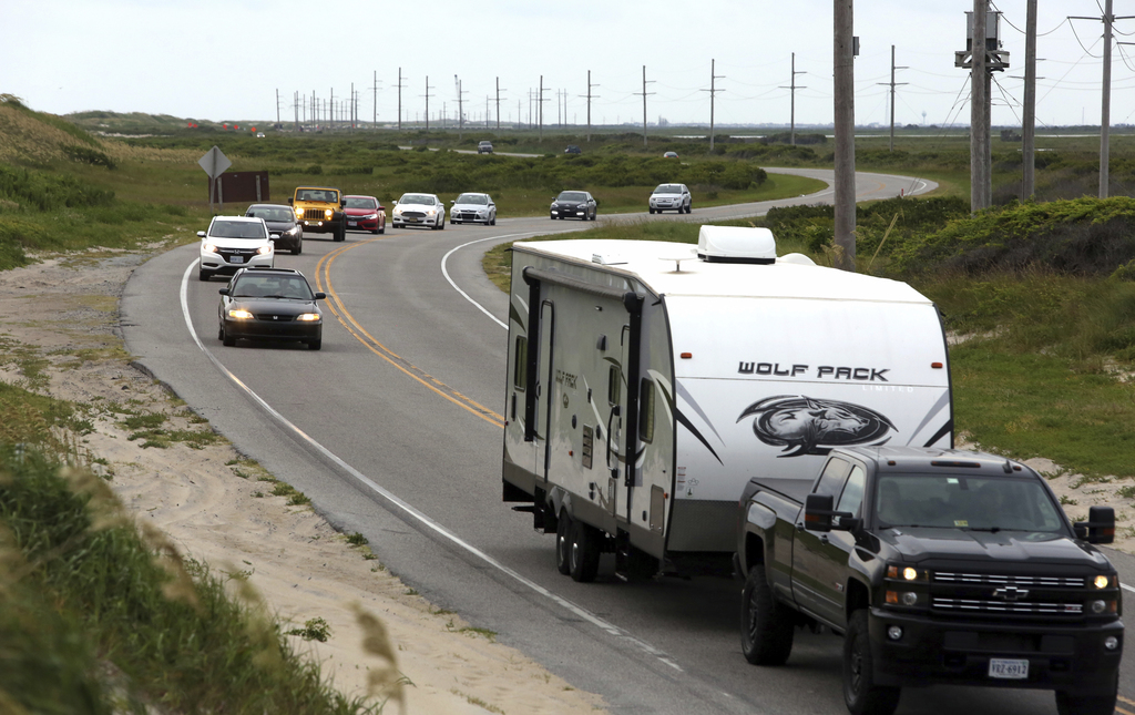 Vacationers head north on NC 12 on Hatteras Island, N.C., on Friday, July 28, 2017.  An estimated 10,000 tourists face a noon deadline Friday for evac...