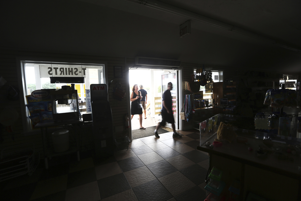 Customers enter the darkened Island Convenience Store in Rodanthe on Hatteras Island, N.C.,  on Friday, July 28, 2017.  An estimated 10,000 tourists f...