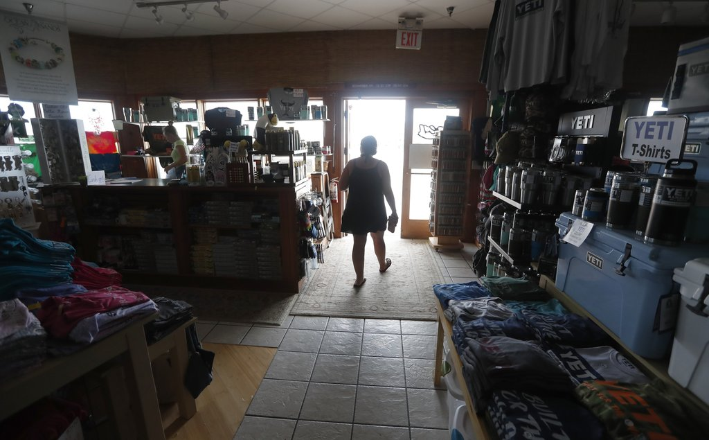 Shoppers, including Tara Clark, shop at Ocracoke Outfitters in Hatteras, N.C. Friday July, 28, 2017. Even though the power was out, Clark and her kids...