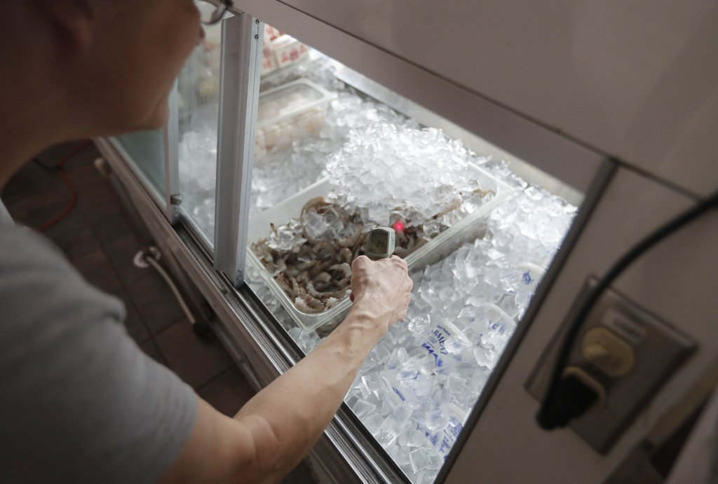 Vicki Harrison checks the temperature of the fish display at Harbor House Seafood in Hatteras, N.C. Friday July, 28, 2017. Even though the power was o...