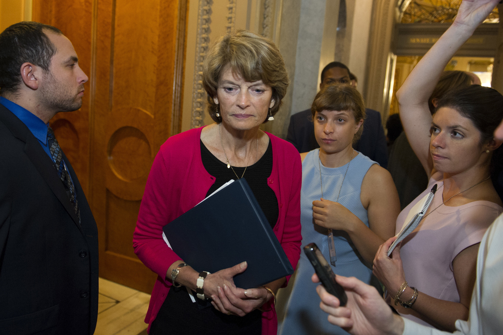 FILE - In this July 28, 2017 file photo, Sen. Lisa Murkowski, R-Alaska passes reporters as she leaves the Senate Chamber on Capitol Hill in Washington...