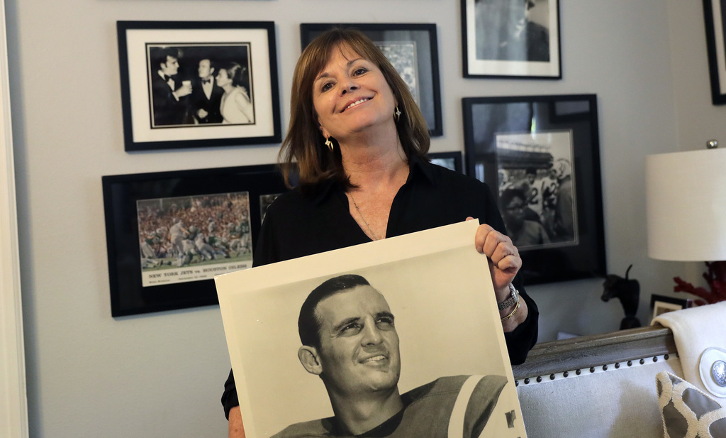 In this Wednesday, July 26, 2017 photo, Lise Hudson poses with photos of her husband, Jim Hudson, who played football for the University of Texas and ...