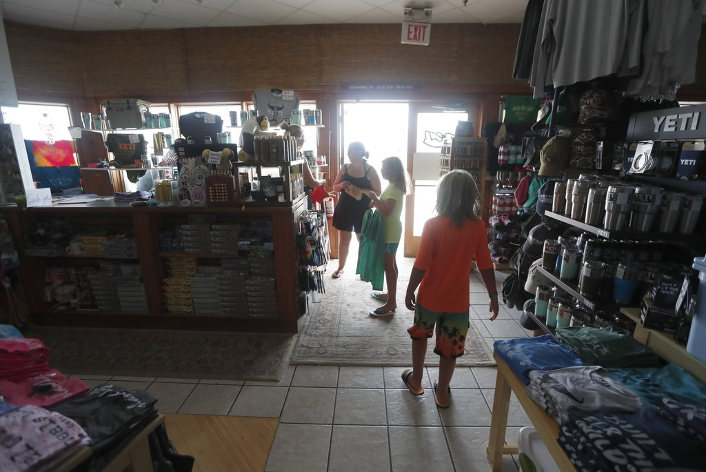 Tara Clark and her children, Eli, 9, and Lucy, 11, shop at Ocracoke Outfitters in Hatteras, N.C. Friday July, 28, 2017. Even though the power was out ...