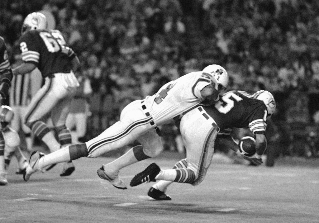 FILE - In this Dec. 2, 1975, file photo, Miami Dolphins quarterback Earl Morrall is tackled by New England Patriots linebacker Steve Zabel during a fo...