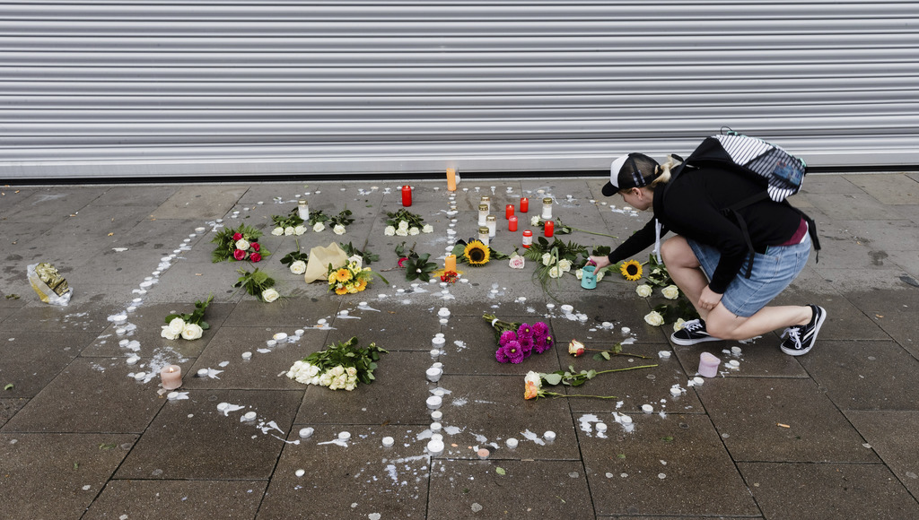 A woman places flowers  near a supermarket in Hamburg, Germany,  Saturday, July 29, 2017. A man armed with a kitchen knife fatally stabbed one person ...