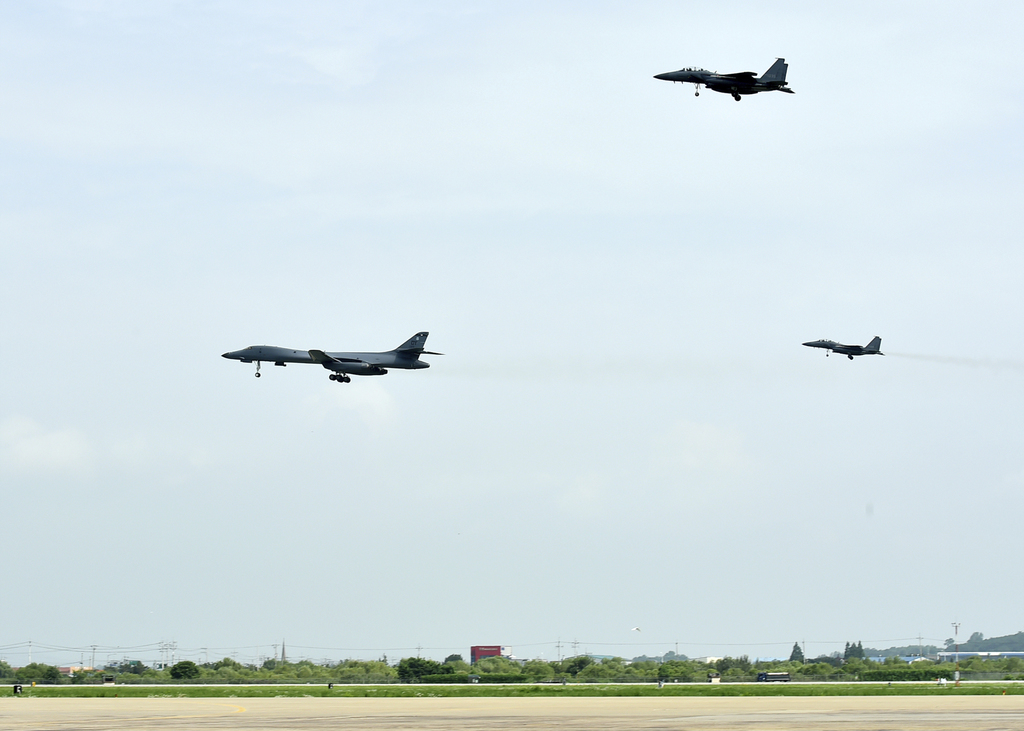 In this photo provided by South Korea Defense Ministry, a U.S. Air Force B-1B bomber, left, flies with South Korean F-15K fighter jets over Osan Air B...