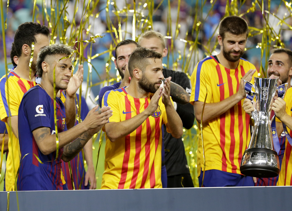 Barcelona's Neymar, left, and his teammates stand with the trophy after defeating Real Madrid 3-2 in an International Champions Cup soccer match, Satu...