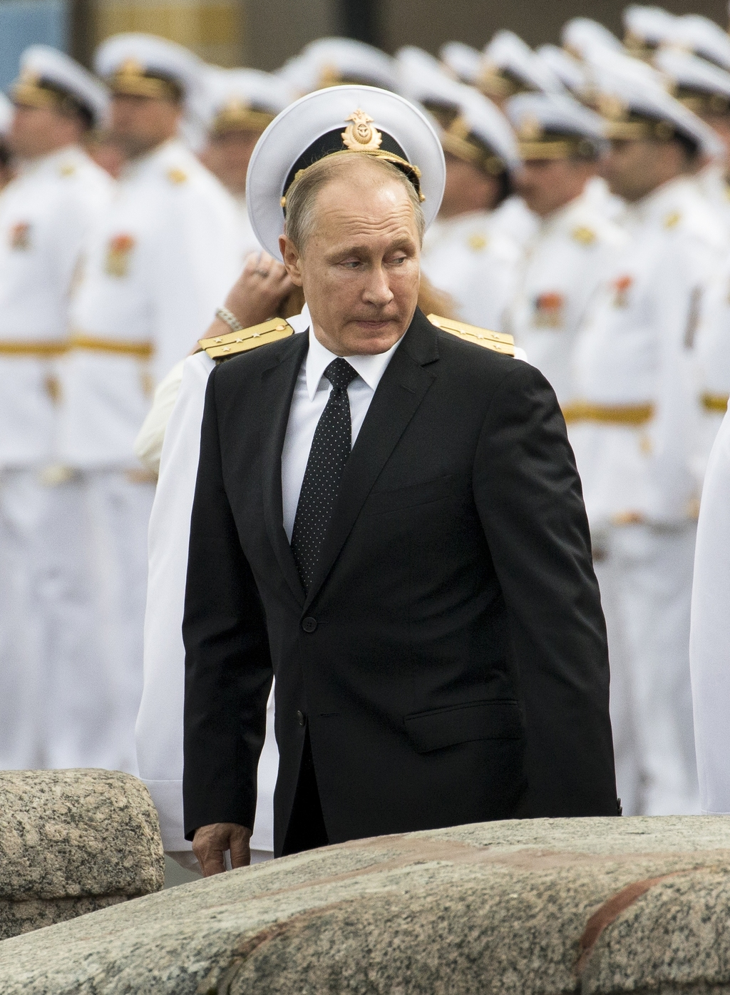 Russian sailors stand in attention as Russian President Vladimir Putin leaves after attending the military parade during the Navy Day celebration in S...