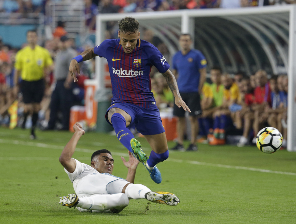 Real Madrid's Casemiro, left, falls to the field as he vies for the ball with Barcelona's Neymar, right, during the first half of an International Cha...