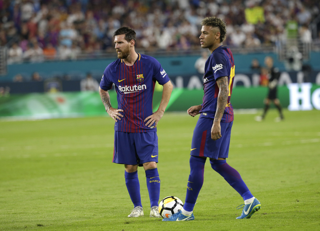 Barcelona's Lionel Messi, left, and Neymar, right, stand on the field during a break in the action during the first half of an International Champions...