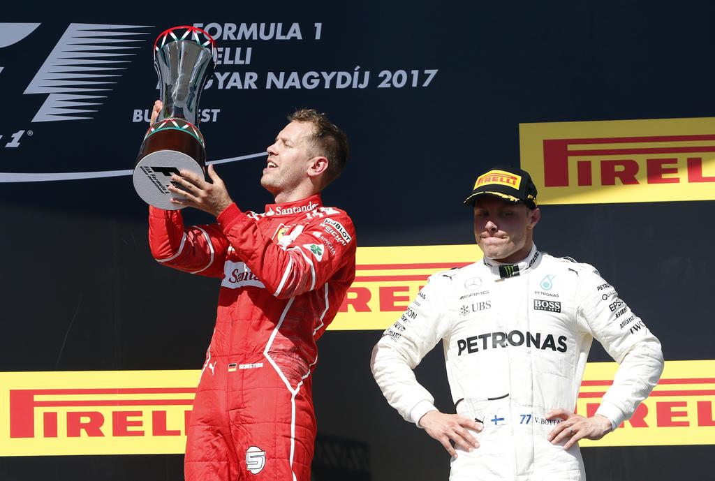 Ferrari driver Sebastian Vettel of Germany holds his winner's trophy next to third placed Mercedes driver Valtteri Bottas of Finland, right, on the po...