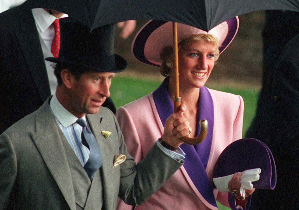 FILE- In this Wednesday, June 20, 1990 file photo, Britain's Princess Diana and Prince Charles, take shelter under an umbrella while attending the sec...