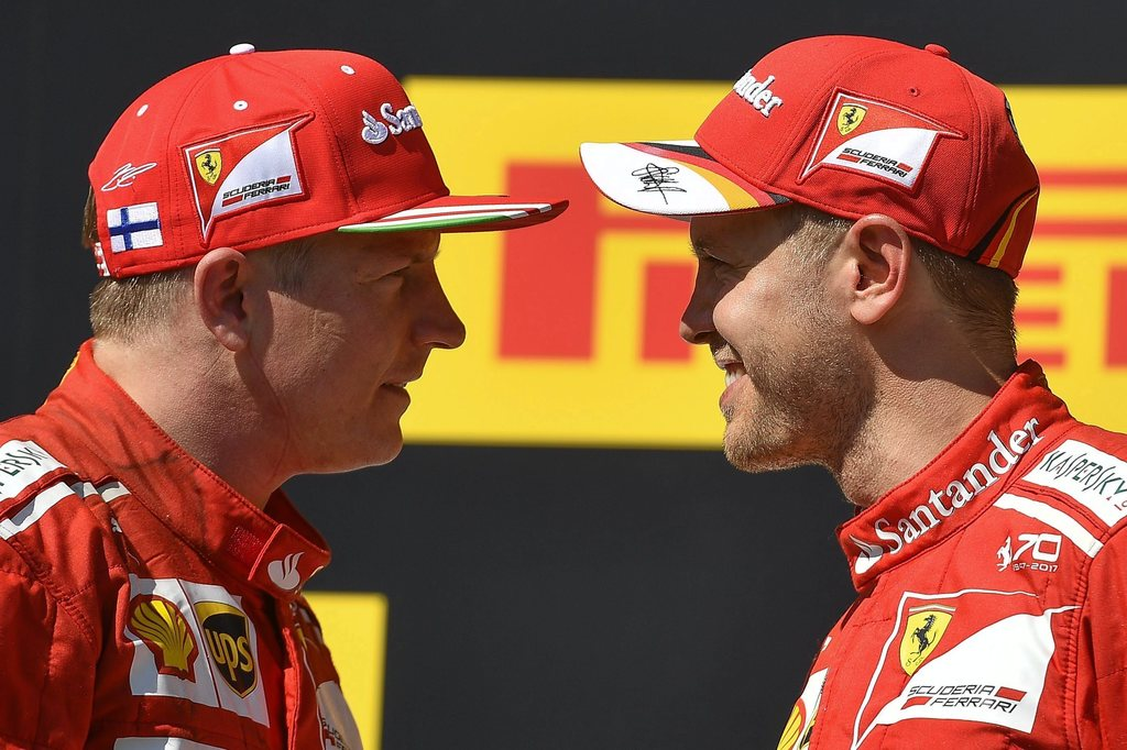 First placed German Sebastian Vettel of Ferrari, right, and his second placed teammate Finnish Kimi Raikkonen stand face to face on the podium after V...