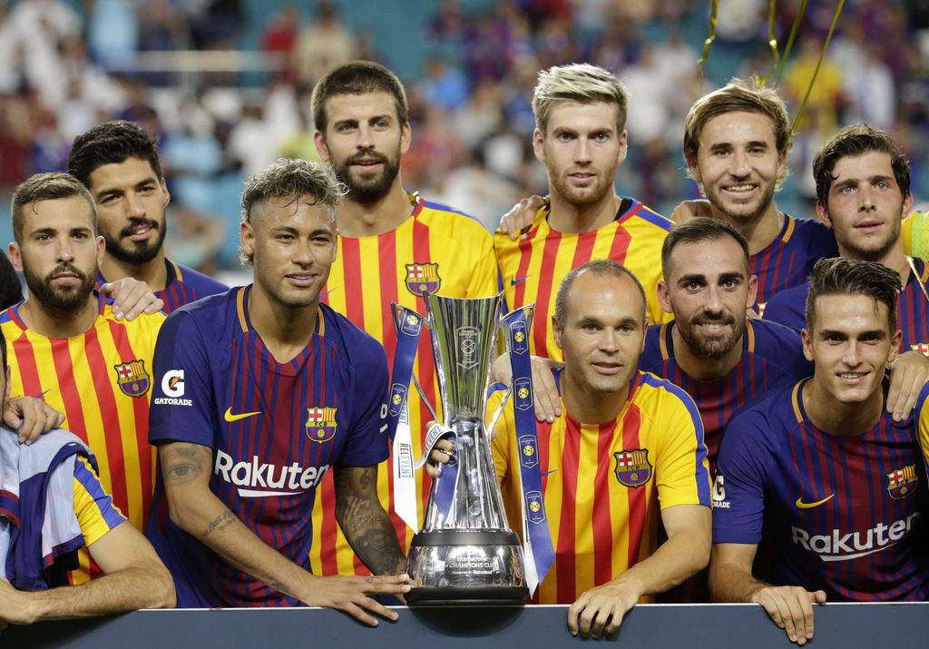 Barcelona's Neymar, second from left front, and teammates pose with the trophy after defeating Real Madrid in an International Champions Cup soccer ma...
