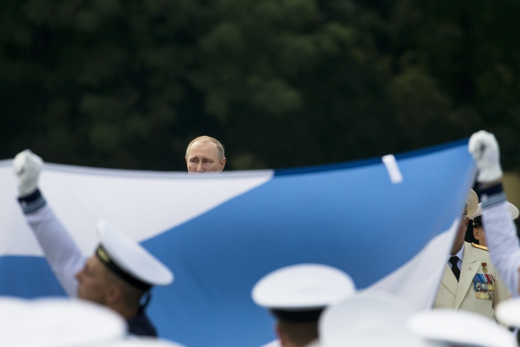 Russian President Vladimir Putin, center, watches as sailors carry a Russian National Navy flag in a military parade during the Navy Day celebration i...