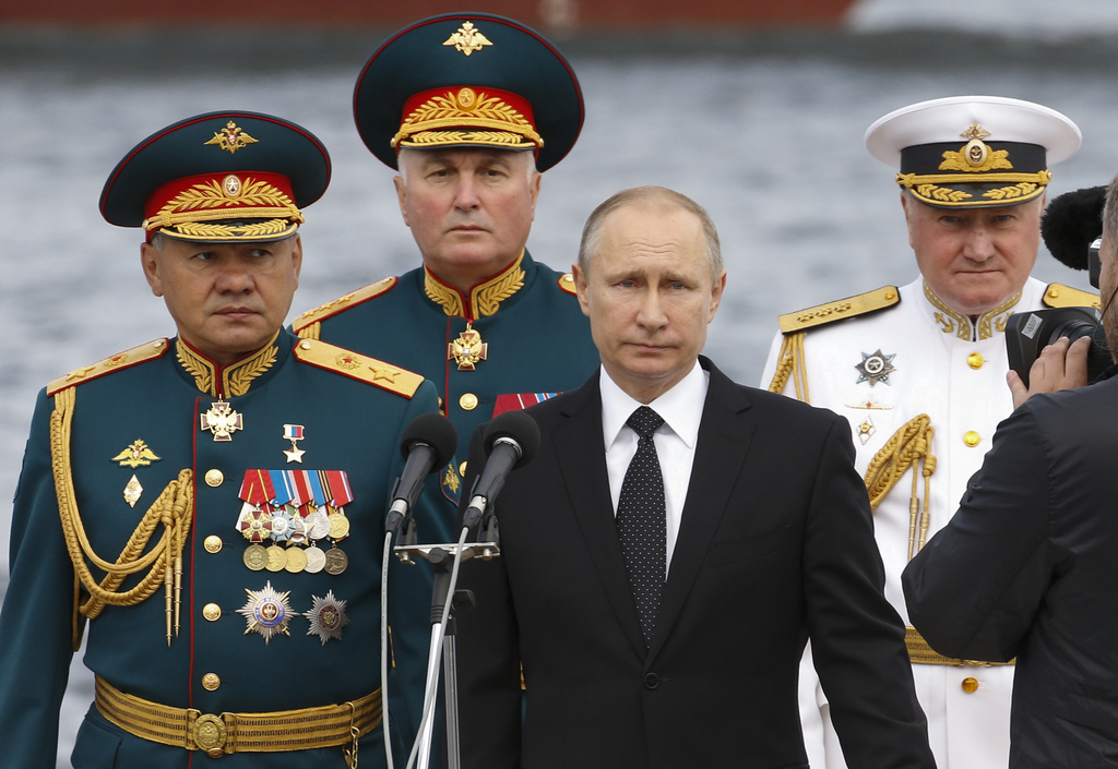 Russian President Vladimir Putin, center, Defence Minister Sergei Shoigu, left, Commander-in-Chief of the Russian Navy Vladimir Korolev, right, and Co...