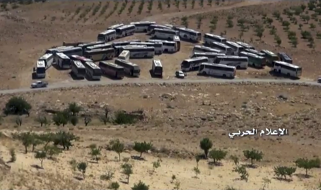 This frame grab from video released on Monday, July 31,2017 and provided by the government-controlled Syrian Central Military Media, shows buses gathe...
